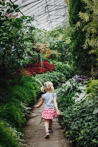 caucasian girl walking on a stone path in a botanical garden greenhouse